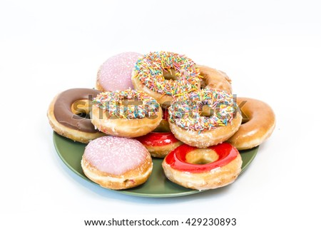 A plate of the  colorful glazed donuts with sprinkles - stock photo