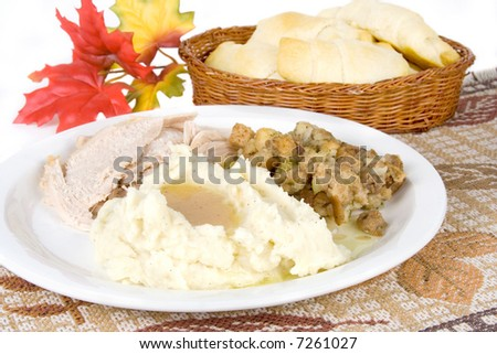 A plate of turkey, mashed potatoes and gravy, and stuffing. Freshly baked rolls in the background. Autumn theme. - stock photo