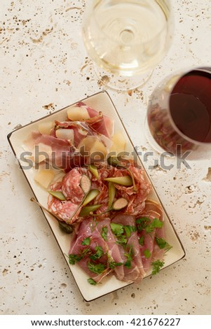 A plate of various deli meat and greens alongside two glasses of wine - stock photo
