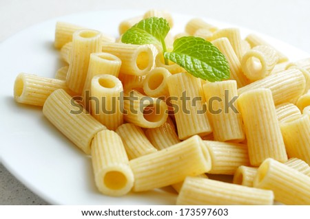a plate with cooked penne rigate - stock photo