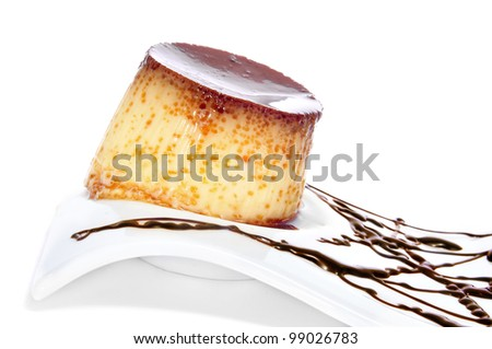 a plate with creme caramel and syrup on a white background - stock photo