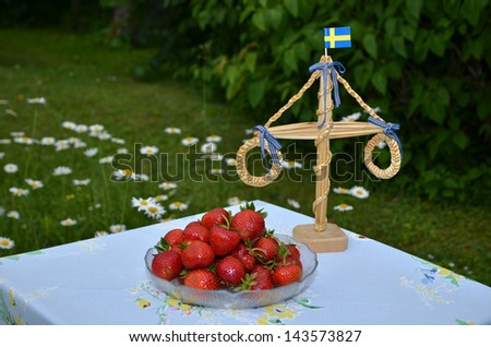 A plate with fresh strawberries and decoration in the garden at midsummer in Sweden. - stock photo