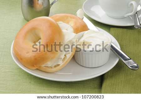 A plate with two sliced bagels with cream cheese - stock photo