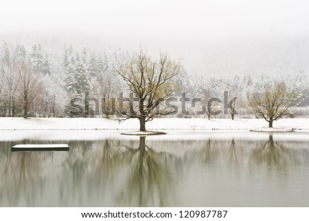 A platform and islands on a calm Catskills lake with snow-covered mountains behind near Big Indian, New York - stock photo