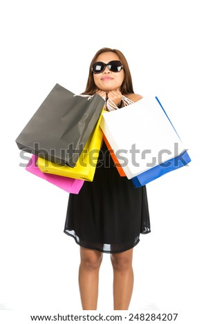 A playful Asian female in elegant black dress, oversized sunglasses hugs colorful department store bags while grinning, chin, face resting on hands. Isolated on white. Thai national of Chinese origin - stock photo