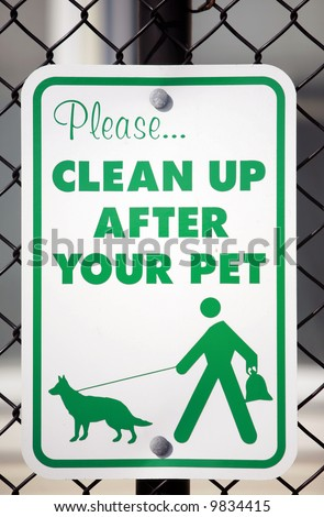 """a """"please clean up after your pet"""" sign in a park - stock photo"""