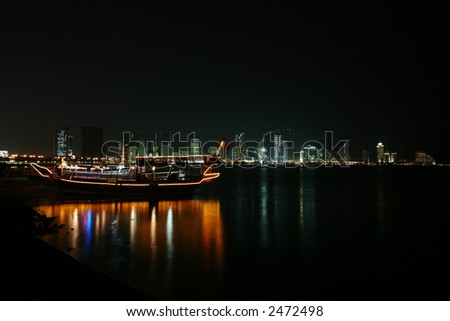 A pleasure dhow on the Corniche in Doha, Qatar, at night, against the high-rise skyline. January 2007 - stock photo