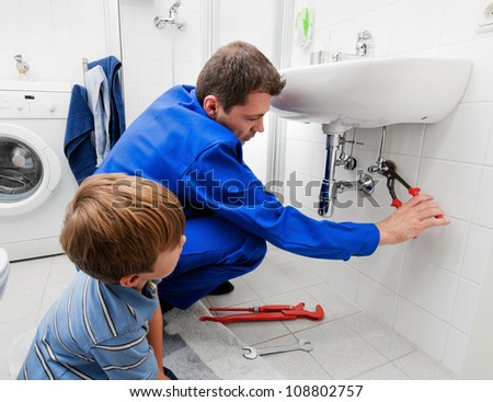 a plumber repairing a broken sink in bathroom - stock photo