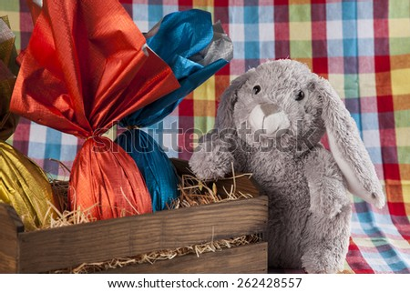 A plush bunny holding a basket of brazilian Easters eggs, on a colored background - stock photo