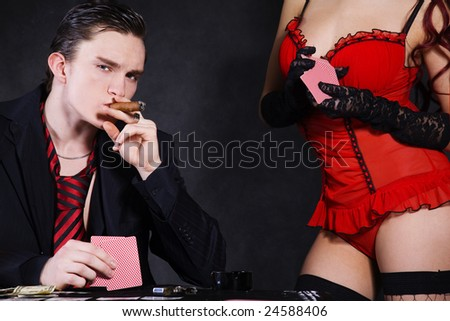 a poker player sitting at a table smoking cigar - stock photo