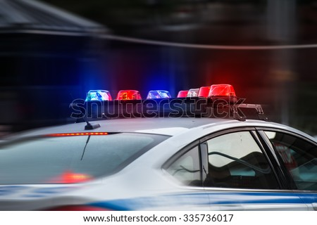 A police car rushes to the emergency call with lights turned on - stock photo