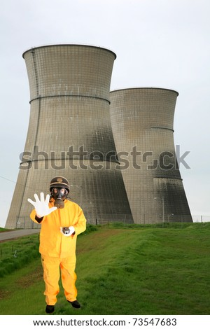 a police man or security guard in a yellow rain suit or anti Radiation Suit is worried about the readings he is getting on his Geiger counter while infront of  Nuclear Generator Cooling Towers - stock photo