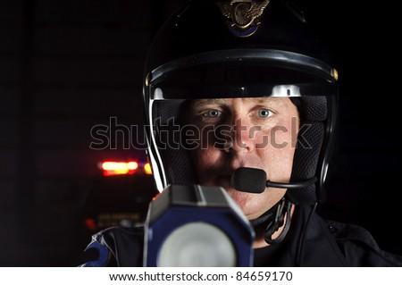 a police officer at night pointing his radar gun at traffic. - stock photo