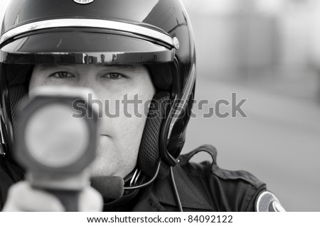 a police officer pointing his radar gun at speeding traffic. - stock photo