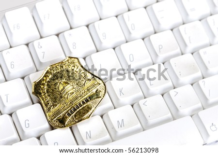 A policeman's badge on a computer keyboard - stock photo