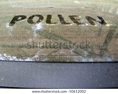 a pollen covered table during the beginning of the Spring season with the word written on it. - stock photo