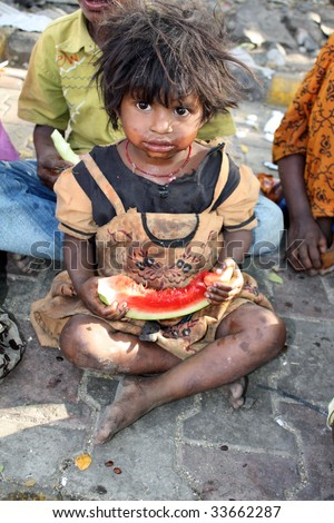 A poor beggar girl from India eating a watermelon. - stock photo