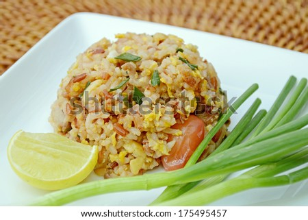 """A popular meal """"Fried Rice"""" served with onion leaves and a piece of lemon. - stock photo"""