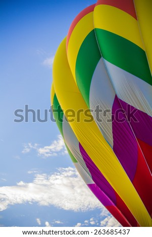 A portion of a colorful hot air balloon sits against a beautiful blue sky. - stock photo
