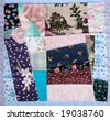 a portion of a crazy quilt with various floral and print fabrics - stock photo