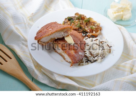 A portion of  battered chicken with rice and mushrooms as a garnish. - stock photo