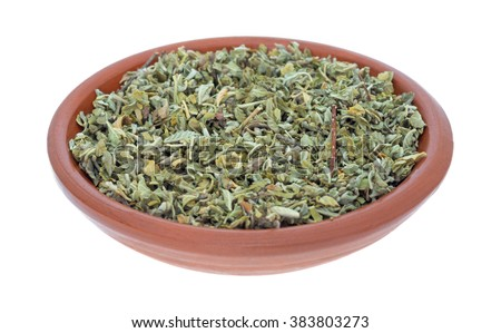 A portion of damiana leaf in a small bowl isolated on a white background. - stock photo