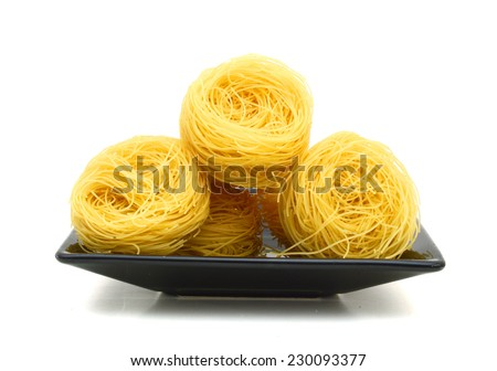 A portion of tagliatelle pasta in plate  isolated on white  - stock photo