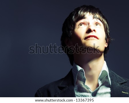 A portrait about a trendy handsome guy who is looking up and he is dreaming something. He is wearing a white shirt and a black suit. - stock photo