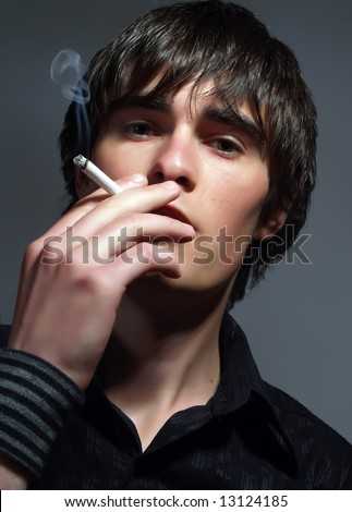 A portrait about a trendy handsome guy who is smoking and he has a glamorous look. He is wearing a stylish black shirt. - stock photo