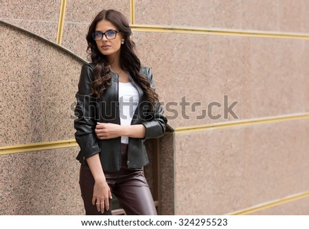 A portrait of a beautiful brunette  young Caucasian woman outdoor. Young smiling woman outdoors portrait. Soft sunny colors.Close portrait. - stock photo