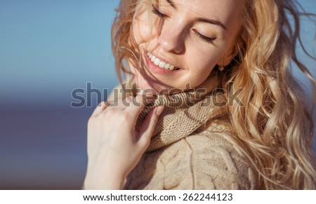 A portrait of a beautiful fair-haired young woman, smiling with her eyed closed and holding her hand on her collar.  - stock photo