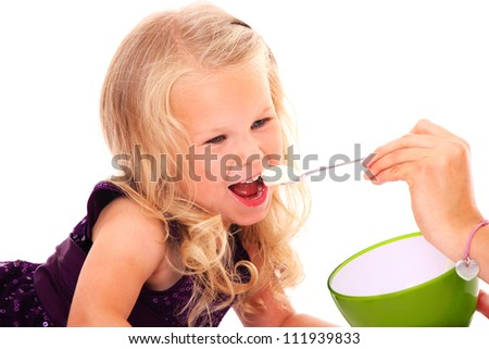 A portrait of a beautiful little girl eating yogurt over white background - stock photo
