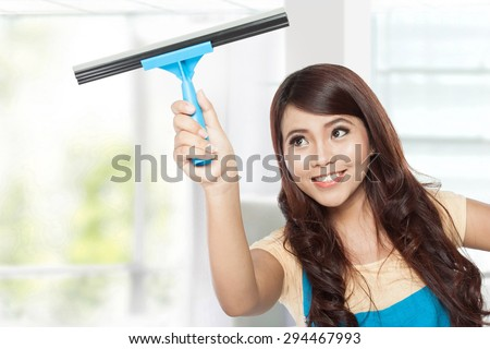 A portrait of a Beautiful young asian women doing domestic chores using glass cleaning wiper - stock photo