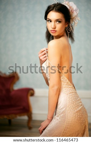 A portrait of a beautiful young bride holding up her shoulder strap and looking over her shoulder - stock photo
