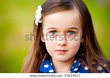 A portrait of a beautiful young girl taken outdoors.  She has a serious express and is making eye contact with the camera. - stock photo