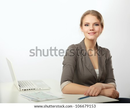 A portrait of a businesswoman sitting at a desk with a laptop - stock photo