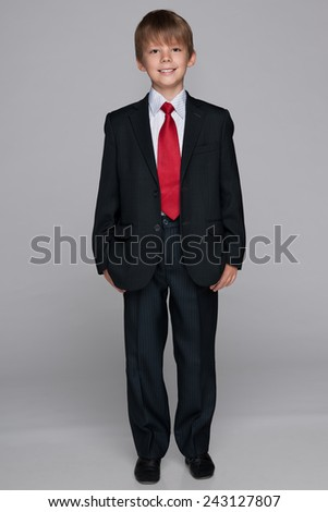 A portrait of a cheerful schoolboy against the gray background - stock photo