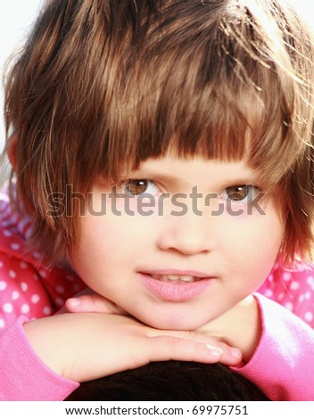A portrait of a cute little beautiful girl resting her head on hands - stock photo