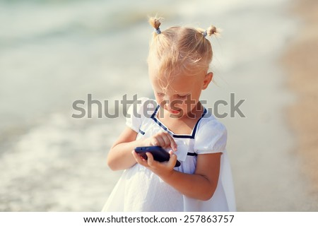 A portrait of a cute little blonde girl in a white dress calling by phone standing on the beach on a warm summer day. Holiday on a seashore concept. Funny kids. Sea. Ocean. - stock photo