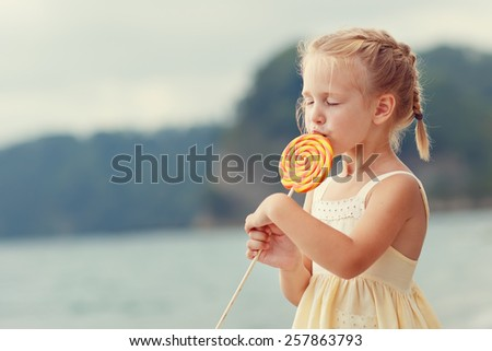 A portrait of a cute little blonde girl in a yellow dress eating a bright orange Lollipop standing on the beach on a warm summer day. Holiday on a seashore concept. Funny kids. Sea. Ocean. - stock photo