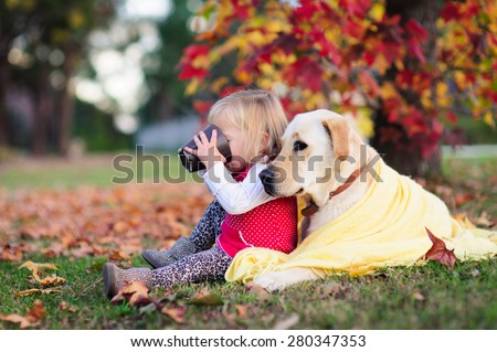 A portrait of a cute little girl drinking tea from a mug and sitting next to her dog, a yellow labrador wrapped up in a warm blanket - stock photo