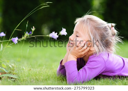 A portrait of a cute little girl lying on the ground in the garden on a nice summer day and  looking at a wild flower - stock photo
