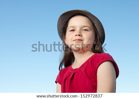 A portrait of a cute little girl, she is standing outside, wearing a hat and a red shirt against a blue sky, - stock photo
