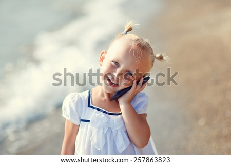 A portrait of a cute little smiling blonde girl in a white dress calling by phone standing on the beach on a warm summer day. Holiday on a seashore concept. Funny kids. Sea. Ocean. - stock photo