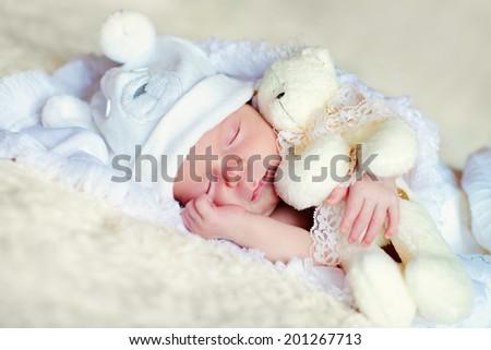 A portrait of a cute newborn baby in a blue like a bear cub hat sleeping with a white teddy bear - stock photo