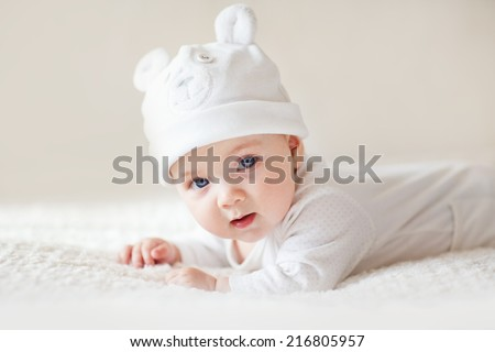 A portrait of a cute newborn baby in a white like a bear cub hat lying on its stomach - stock photo
