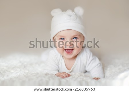 A portrait of a cute newborn baby in a white like a bear cub hat lying on its stomach and laughing - stock photo