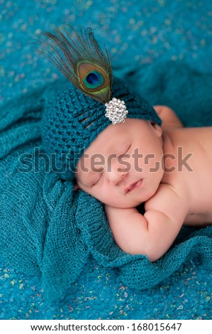 A portrait of a 12 day old sleeping newborn baby girl wearing an elegant teal flapper hat with rhinestone button and peacock feather. - stock photo