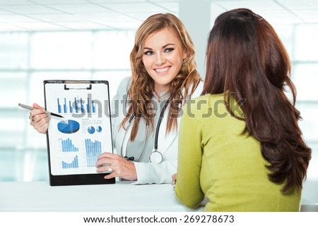 A portrait of a Doctor with female patient. Friendly, Happy Doctor with Stethoscope explaining to Patient in Clinic - stock photo