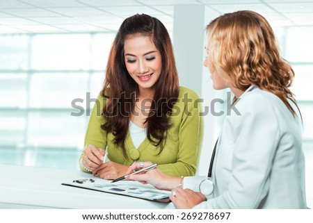 A portrait of a Doctor with female patient. Friendly, Happy Doctor with Stethoscope Giving Advice to Patient in Clinic - stock photo